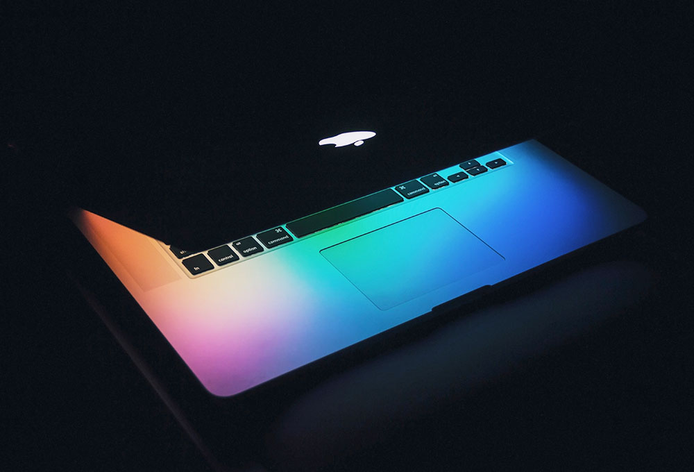 Diversity and inclusion in development and R&D - Picture of laptop with multiple rainbow colors from screen illuminating keyboard
